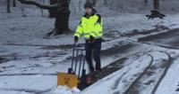 International business management degree student Will Marston in high vis jacket clearing snow