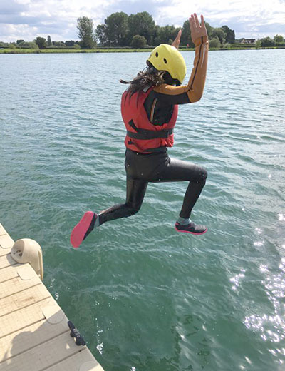 Girl jumping into the lake