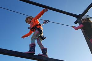girl climbing on outdoor wire frame