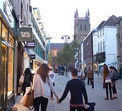 People walking away from the camera on Worcester High Street, with the Cathedral in the distance.