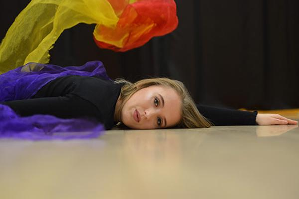 Female student lying on the floor, facing camera with multi-coloured scarves