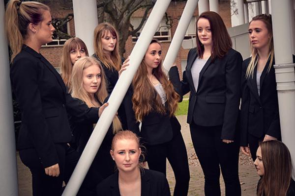 Women in dark suits stand among pillars