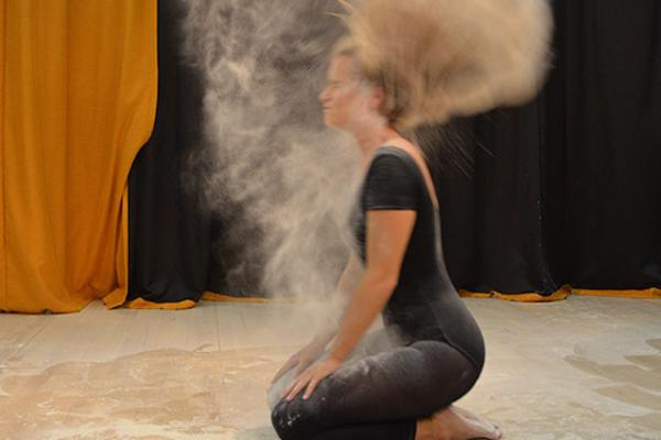 Female student in black throws hair back in cloud of dust