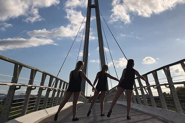 Three dancers on footbridge silhouetted against blue sky