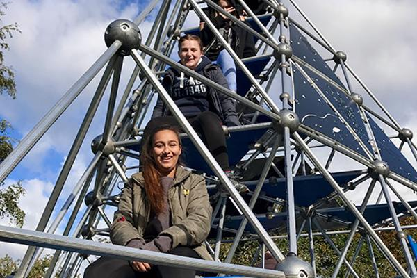 Students sit on pyramid climbing frame