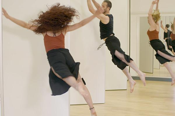 Male and female dancer leap in front of mirror