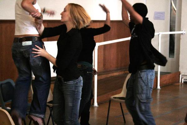 Drama degree students dancing on and around chairs
