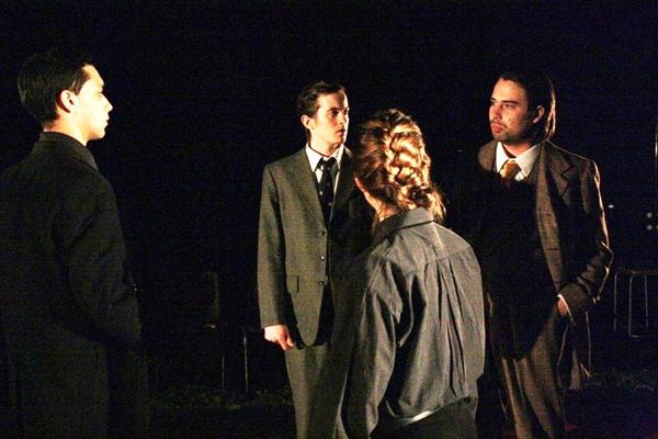 Performance shot of drama degree students in suits in darkened drama studio