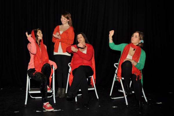 Performance shot of four drama degree students in red on white chairs.