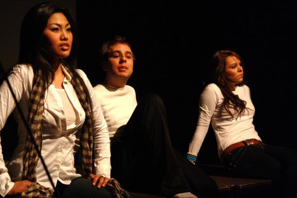 Performance picture of three drama degree students sitting in various poses and staring in different directions.