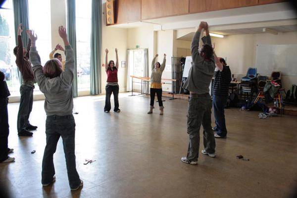 Drama degree students stand in a circle in a well-lit room with their hands above their heads.