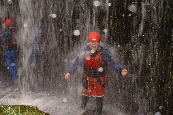 Person in protective clothing and helmet standing under a waterfall