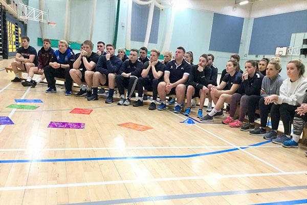 Group of PGCE Secondary Physical Education students sitting on benches in sports halls