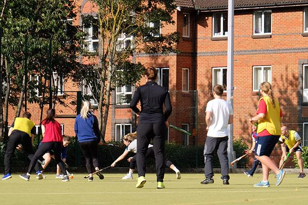 Students playing hockey on astroturf