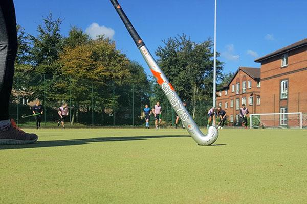 Close-up of hockey stick on astroturf with University halls of residence in background