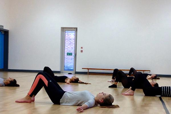 Group of students performing movements while lying on the floor