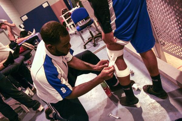 Sports therapists strapping a leg
