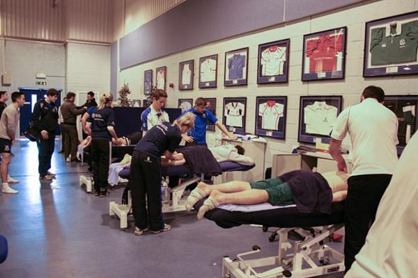 Room of multiple athletes being treated by sport therapists