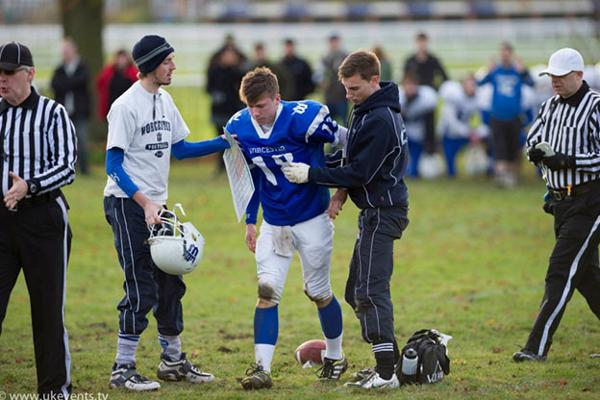 Sports therapist assists American football player on the field