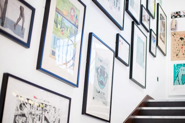 Student artwork framed and displayed in stairway