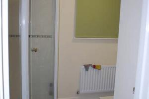 part of a bathroom showing a shower a mirror and the end of a bath