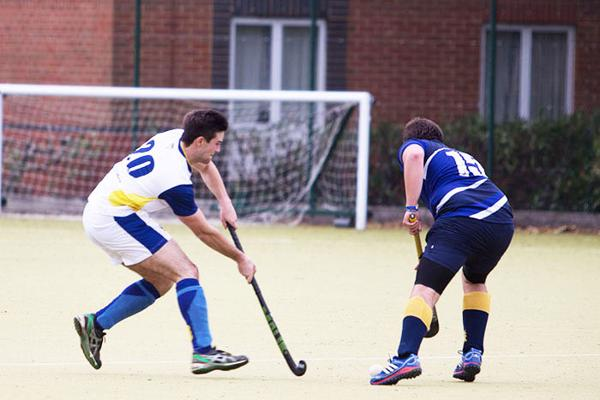 men playing hockey on an outside pitch