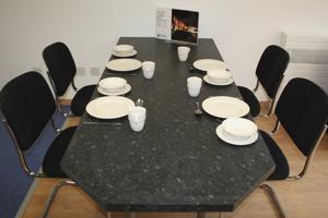 empty chairs surrounding a table with white crockery