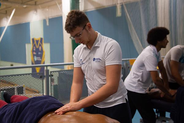 one sports therapy student massaging