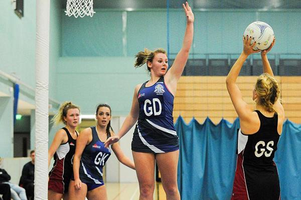 women playing netball in a gym
