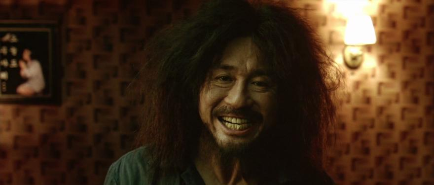 A still from the film Oldboy of a man with extremely backcombed hair grimacing