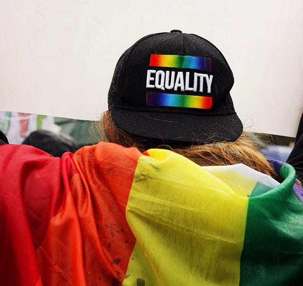 A person, viewed from behind, is wearing a Gay pride hat