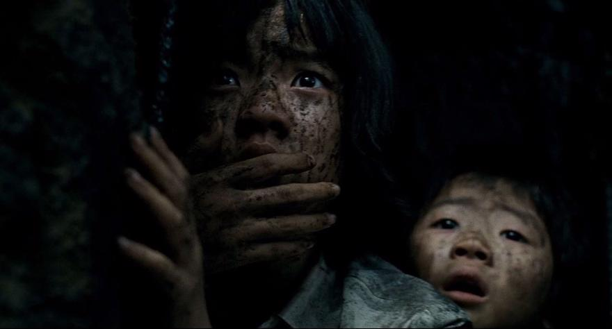 A still from the film The Host featuring two children covered in dirt looking at the camera