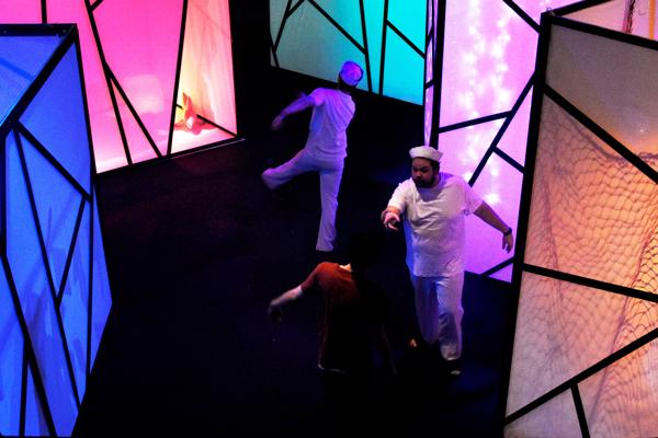 Two people dressed in white are stretching on a brightly coloured stage