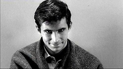 A man stares menacingly into the camera in a black and white film still