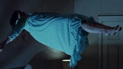 A girl is levitating above a bed in this film still