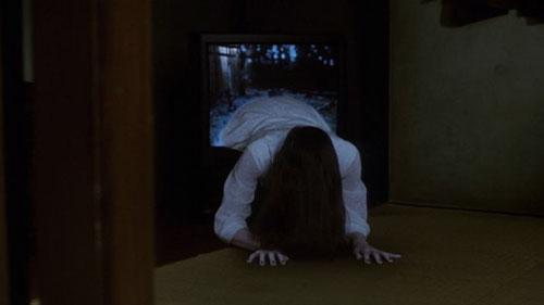 A long haired girl crawls out from inside a television in this film still