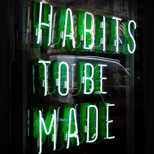 "The Words ""Habits to be Made"" lit up in neon"""