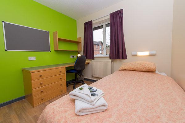 A bedroom inside University of Worcester accommodation. There is a single bed, a large pin board, desk, chest of drawers and a window in the room.