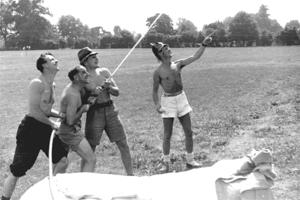 Four shirtless men wearing fireman's helmets and using a hose