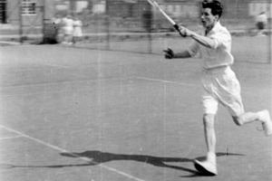 Woman playing tennis in white kit