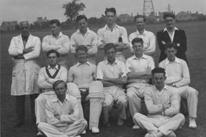 A group of men dressed in cricket whites.