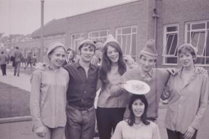A group of people wearing hats outside the university in the 1960s