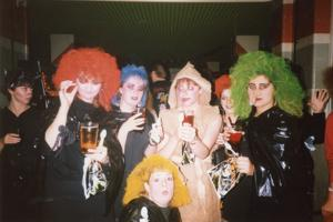 A group of women are in Halloween fancy dress as witches with brightly coloured hair and mummies wrapped in paper