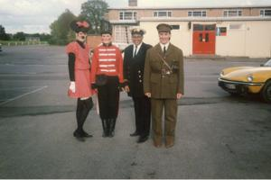 A group of women in fancy dress stand outside a university building. One is Minnie Mouse, one is wearing a red soldier uniform, one is a navy captain and one is dressed as a world war two soldier.