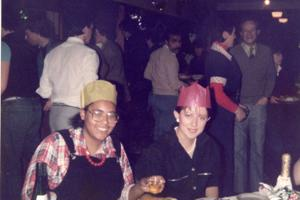 Two women in 1980s clothing and paper party hats sit in front of party food