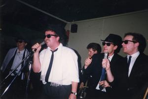 Five men wearing sunglasses and suits are singing into microphones in the 1980s
