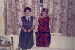 Two women in 1980s party dresses standing against a window