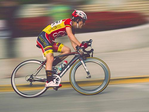A brightly dressed competitive cyclist competes against a blurred background.