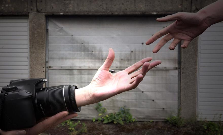 A photo of two hands reaching for each other. One hand is coming out from a camera.