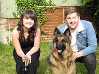 Megan Davis and a man dressed in a denim jacket are sitting in a garden next to an Alsatian dog.